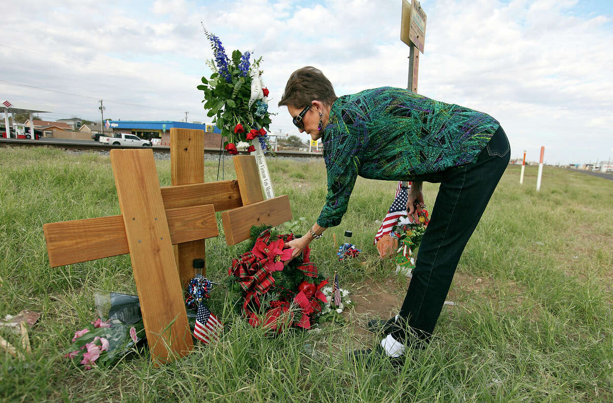 Pat Moore, 66, lays a wreath at the intersection, Sunday Nov. 18, 2012, in Midland, Tx., where a Union Pacific train struck a float carrying military veterans on Thursday Nov. 15, 2012, killing four men, including one from the San Antonio area.