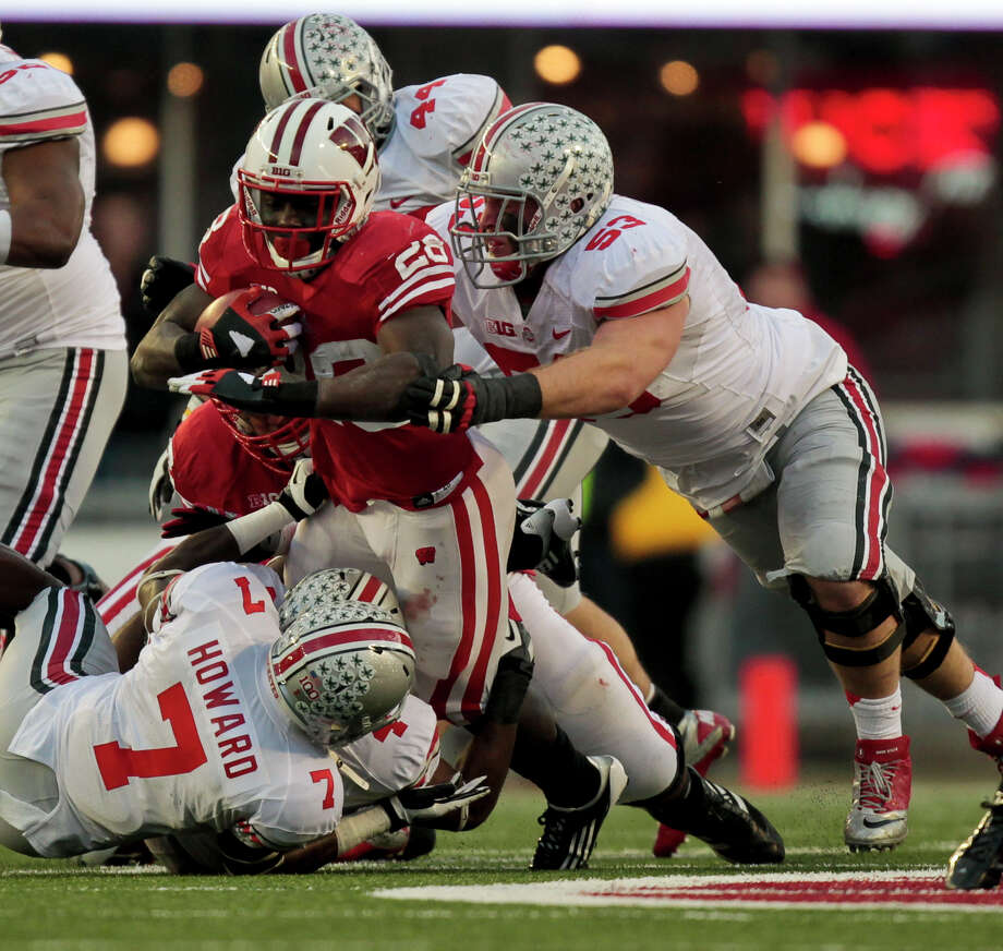 Ohio State's Travis Howard (7) and Garrett Goebel (53) wrap up Wisconsin's Montee Ball during the first half of a college football game Saturday, Nov. 17, 2012, in Madison, Wis. Ohio State won 21-14 in overtime. (AP Photo/Andy Manis) Photo: Andy Manis, Wires / FR19153 AP