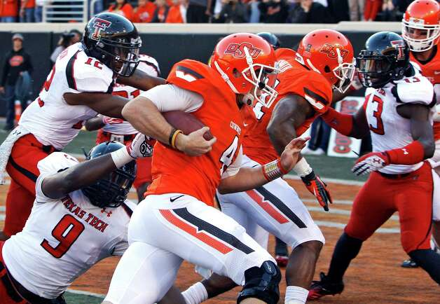 Oklahoma State quarterback J.W. Walsh (4) runs past Texas Tech linebacker Shawn Corker (9) for a touchdown in the second quarter of an NCAA college football game in Stillwater, Okla., Saturday, Nov. 17, 2012. (AP Photo/Sue Ogrocki) Photo: Sue Ogrocki, Wires / AP