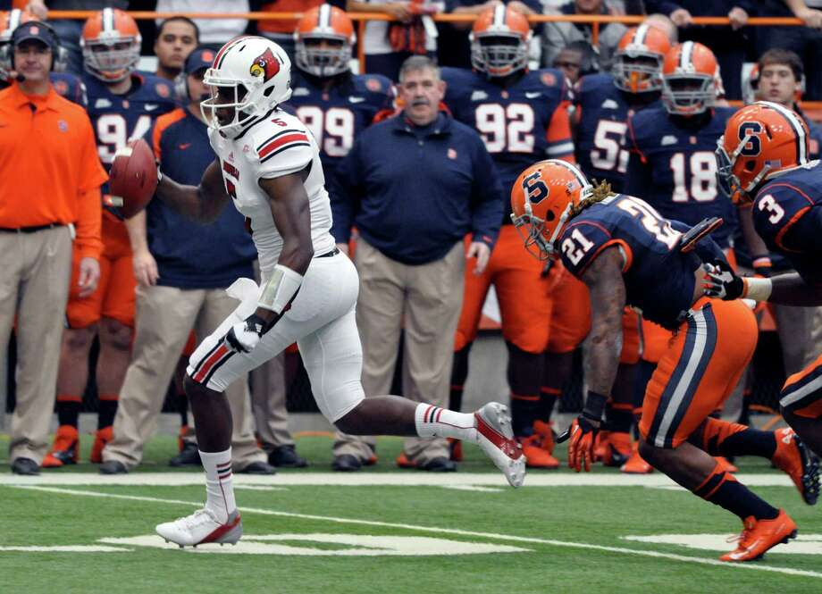 Louisville's Teddy Bridgewater is chased out of the pocket by Syracuse's Shamarko Thomas (21) and Durell Eskridge during the second quarter of an NCAA college football game in Syracuse, N.Y., Saturday, Nov. 10, 2012. Syracuse won 45-26. (AP Photo/Kevin Rivoli) Photo: KEVIN RIVOLI, Wires / FR60349 AP