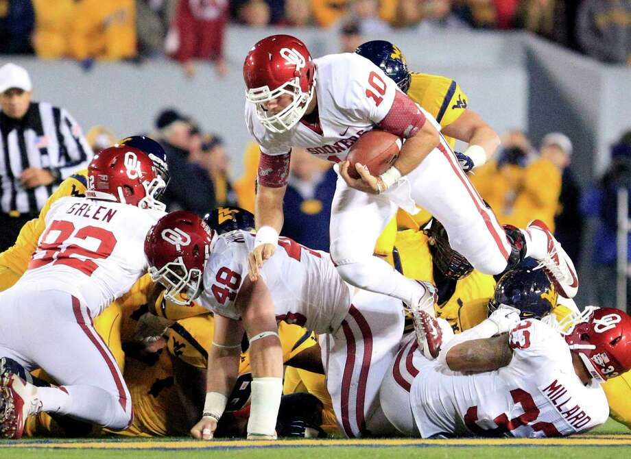 Oklahoma's Blake Bell (10) carries the ball during the third quarter of their NCAA college football game against West Virginia in Morgantown, W.Va., on Saturday, Nov. 17, 2012. Oklahoma won 50-49. (AP Photo/Christopher Jackson) Photo: Christopher Jackson, Wires / FRE 170573 AP