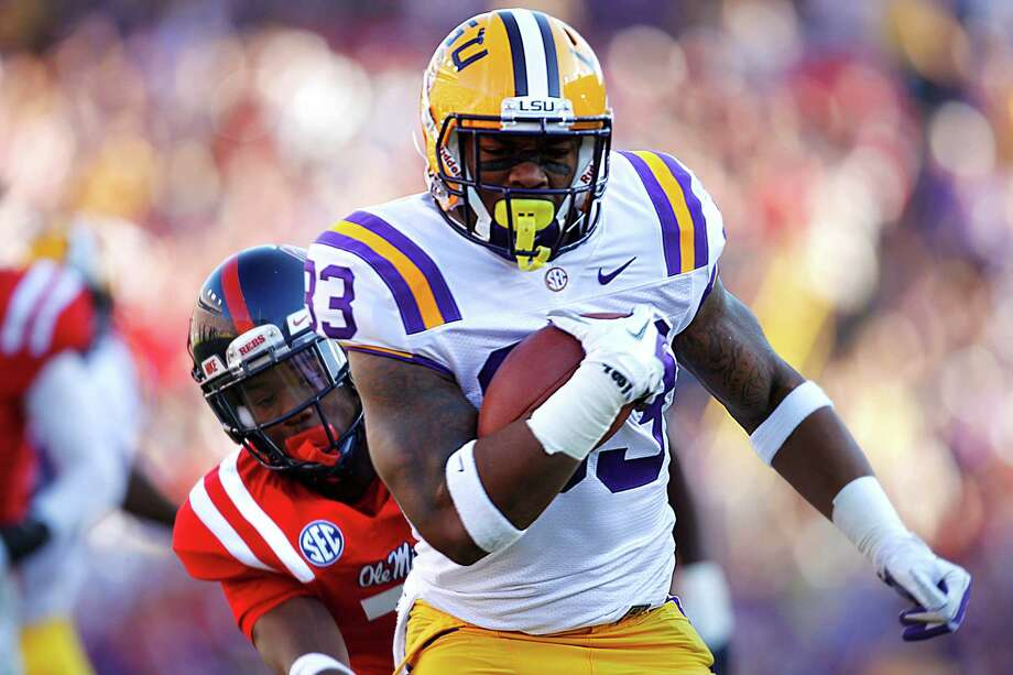 LSU running back Jeremy Hill (33) rushes past Mississippi defensive back Trae Elston (7) on a 27-yard touchdown carry during the first half of their NCAA college football game, Saturday, Nov. 17, 2012, in Baton Rouge, La. (AP Photo/Gerald Herbert) Photo: Gerald Herbert, Wires / AP