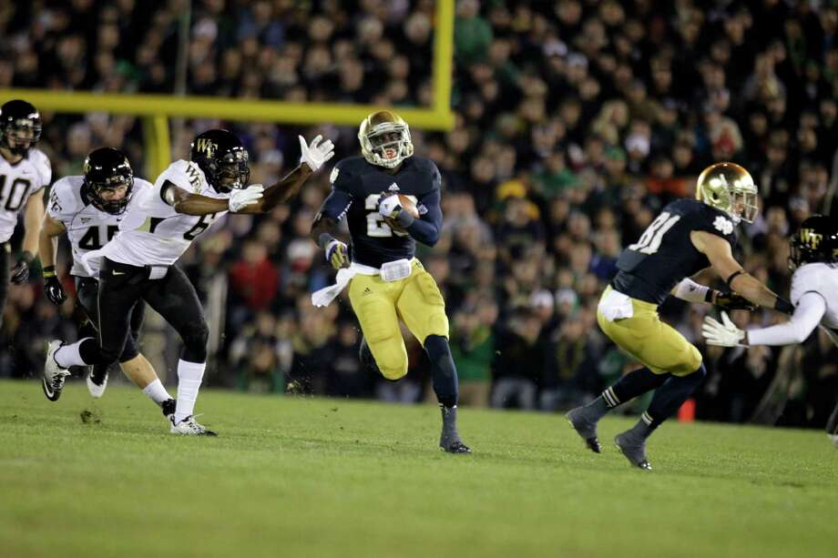Notre Dame running back Cierre Wood (20) cuts around Wake Forest defenders as he picks up 42 yards during the second half of an NCAA college football game in South Bend, Ind., Saturday, Nov. 17, 2012. Notre Dame defeated Wake Forest 38-0. (AP Photo/Michael Conroy) Photo: Michael Conroy, Wires / AP