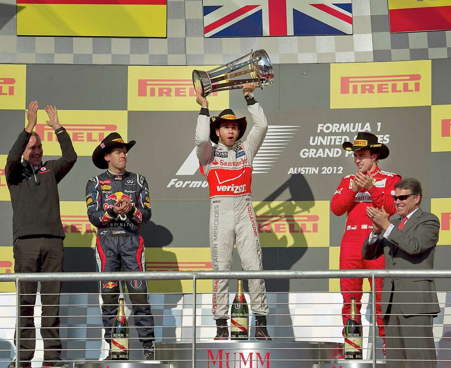 Sunday's inaugural race kicks off in fine fashion as Lewis Hamilton, center, with Vodafone McLaren Mercedes, won the first ever Grand Prix held in Austin, Texas, as he celebrates with Sebastian Vettel, Red Bull Racing, second place, and Fernando Alonso, right, with Scuderia Ferrari, who finished third on the victory podium, November 18, 2012. At far right is Texas Gov. Rick Perry who presented the championship trophy to Hamilton. (Ralph Barrera/Austin American-Statesman/MCT) Photo: Ralph Barrera, McClatchy-Tribune News Service / Austin American-Statesman