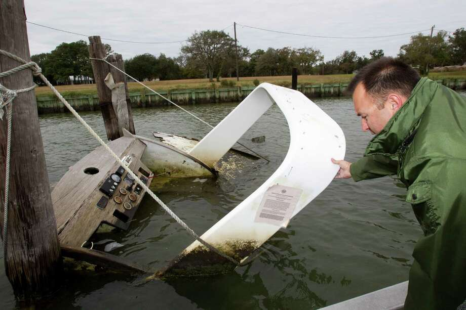 Craig Cook, of the Texas General Land Office, inspects an abandoned boat near Dickinson Bayou in Texas City. The state removal program, funded primarily by federal grants, has 297 derelict boats on its waiting list. Photo: Brett Coomer, Houston Chronicle / © 2012 Houston Chronicle