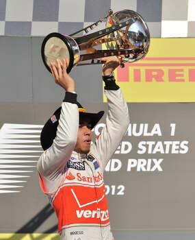 Lewis Hamilton hoists the winners trophy after the United States Grand Prix Sunday at the Circuit of the America's in Austin. Photo: Express-News