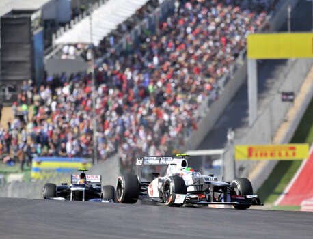 In front of a huge crowd, Mexican driver Sergio Perez leads Brazil's Bruno Senna during the United States Grand Prix Sunday at the Circuit of the America's in Austin. Photo: Express-News