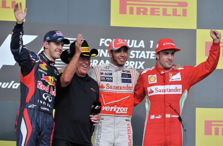 Lewis Hamilton (2nd from right) celebrates winning the US Grand Prix with 2nd place finisher Sebastian Vettel (left) racing legend Mario Andretti (2nd from left) and 3rd place finisher Fernando Alonso (right)after the race Sunday. Photo: Express-News