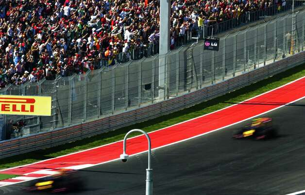 The crowd watches as Red Bull Racing drivers Sebastian Vettel (L) of Germany  and teammate Mark Webber of Britain finish their first lap during the United States Formula One Grand Prix at the Circuit of the Americas on November 17, 2012 in Austin, Texas.     AFP PHOTO/Jim WATSONJIM WATSON/AFP/Getty Images Photo: JIM WATSON, Getty Images / AFP