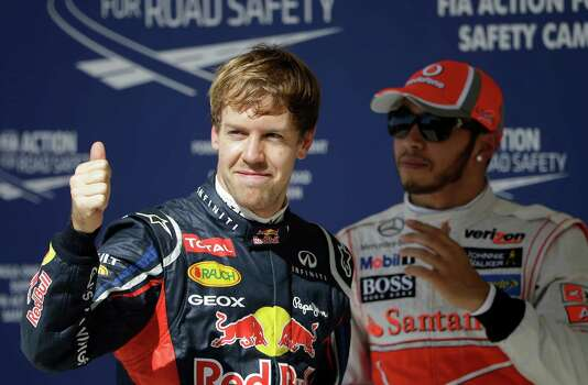 Red Bull driver Sebastian Vettel of Germany reacts in front of McLaren Mercedes driver Lewis Hamilton of Britain, after winning the pole for the Formula One U.S. Grand Prix auto race at the Circuit of the Americas Saturday, Nov. 17, 2012, in Austin, Texas.  Hamilton will start second. (AP Photo/David J. Phillip) Photo: David J. Phillip, Associated Press / AP