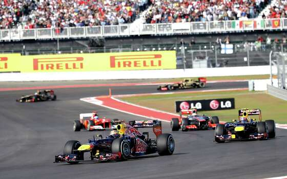 Red Bull driver Sebastian Vettel, left, of Germany, steers his car during the Formula One U.S. Grand Prix auto race at the Circuit of the Americas Sunday, Nov. 18, 2012, in Austin, Texas. (AP Photo/David J. Phillip) Photo: David J. Phillip, Associated Press / AP