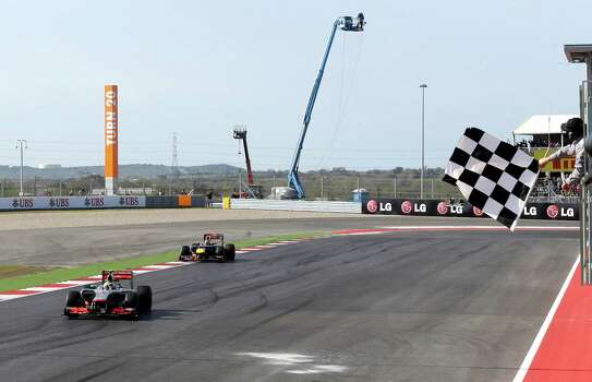 McLaren Mercedes driver Lewis Hamilton of Britain takes the checked flag to win the Formula One U.S. Grand Prix auto race at the Circuit of the Americas Sunday, Nov. 18, 2012, in Austin, Texas. (AP Photo/Luca Bruno) Photo: Luca Bruno, Associated Press / AP