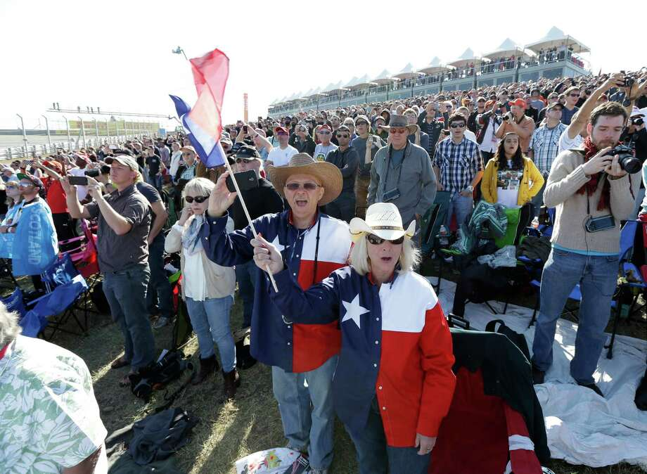 Leslie Lefebvere, right, and Tim Jones from El Paso, Texas cheer during a support race before the Formula One U.S. Grand Prix auto race at the Circuit of the Americas Sunday, Nov. 18, 2012, in Austin, Texas. (AP Photo/David J. Phillip) Photo: David J. Phillip, Associated Press / AP
