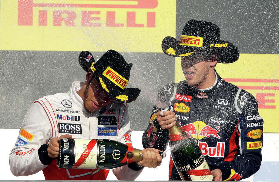 McLaren Mercedes driver Lewis Hamilton, left, of Britain, is sprayed by Red Bull driver Sebastian Vettel, of Germany, after Hamilton won  the Formula One U.S. Grand Prix auto race at the Circuit of the Americas Sunday, Nov. 18, 2012, in Austin, Texas. (AP Photo/Eric Gay) Photo: Eric Gay, Associated Press / AP