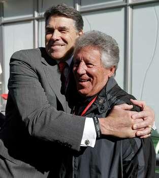 Texas Gov. Rick Perry, left, hugs Mario Andretti before the Formula One U.S. Grand Prix auto race at the Circuit of the Americas Sunday, Nov. 18, 2012, in Austin, Texas. (AP Photo/Darron Cummings) Photo: Darron Cummings, Associated Press / AP
