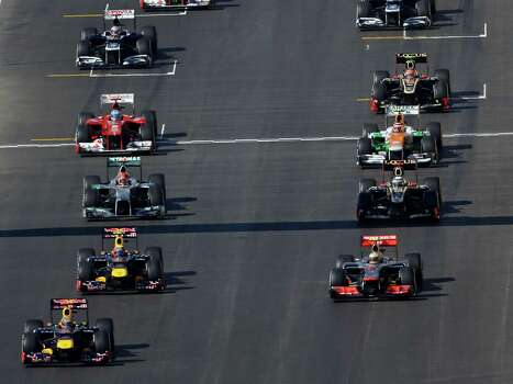Red Bull driver Sebastian Vettel, front left, of Germany leads the field away from the starting grid for the Formula One U.S. Grand Prix auto race at the Circuit of the Americas Sunday, Nov. 18, 2012, in Austin, Texas. (AP Photo/Eric Gay) Photo: Eric Gay, Associated Press / AP