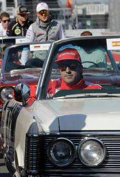 Ferrari driver Fernando Alonso of Spain followed by Mercedes Grand Prix driver Michael Schumacher of Germany board vintage carsduring the drivers parade prior to the start of the Formula One U.S. Grand Prix auto race, at the Circuit of the Americas race track, in Austin, Texas, Sunday, Nov. 18, 2012. (AP Photo/Luca Bruno) Photo: Luca Bruno, Associated Press / AP