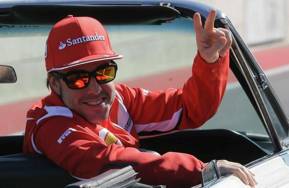 Ferrari driver Fernando Alonso of Spain gestures as he runs on a vintage car during the drivers parade prior to the start of the Formula One U.S. Grand Prix auto race, at the Circuit of the Americas race track, in Austin, Texas, Sunday, Nov. 18, 2012. (AP Photo/Luca Bruno) Photo: Luca Bruno, Associated Press / AP
