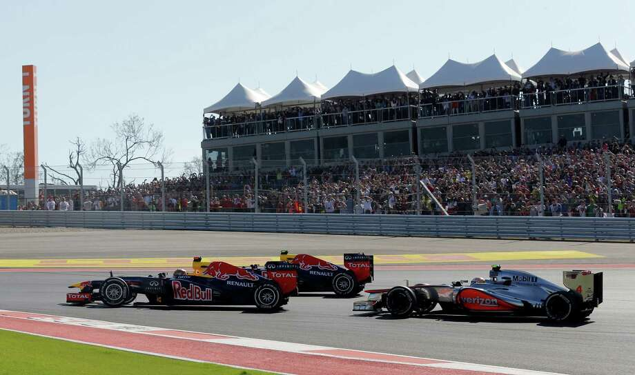 Red Bull driver Sebastian Vettel of Germany leads his teammate, Red Bull driver Mark Webber of Australia and McLaren Mercedes driver Lewis Hamilton, right, of Britain into the first turn during  the Formula One U.S. Grand Prix auto race at the Circuit of the Americas Sunday, Nov. 18, 2012, in Austin, Texas. (AP Photo/Luca Bruno) Photo: Luca Bruno, Associated Press / AP