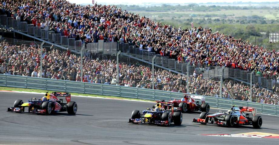 Red Bull driver Sebastian Vettel, second from right, of Germany leads the field into the first turn for the start of the Formula One U.S. Grand Prix auto race at the Circuit of the Americas Sunday, Nov. 18, 2012, in Austin, Texas. (AP Photo/Darron Cummings) Photo: Darron Cummings, Associated Press / AP