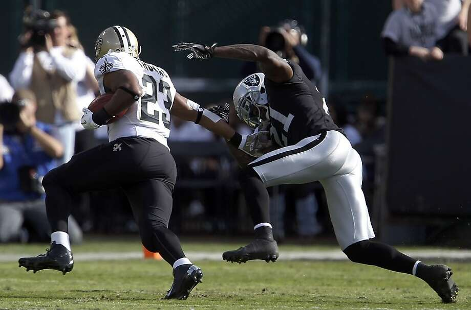 Pierre Thomas(23) stiff arms Ron Bartell for a short gain in the first half. The Oakland Raiders played the New Orleans Saints at O.co Coliseum in Oakland, Calif., on Sunday, November 18, 2012. The Saints defeated the Raiders 38-17. Photo: Carlos Avila Gonzalez, The Chronicle