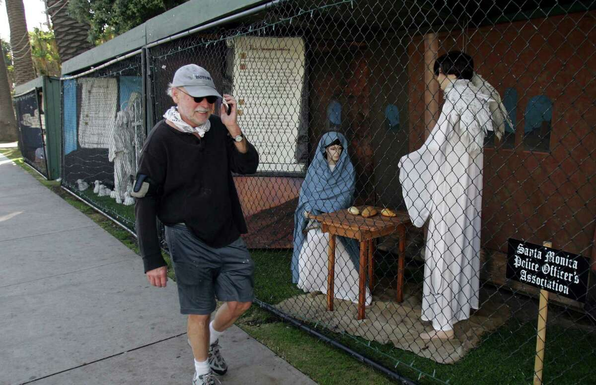 A man walks past Nativity scenes last December in Santa Monica, Calif. Atheist activist Damon Vix last year won two-thirds of the booths in the city-sponsored lottery for spaces in the life-sized Nativity display.