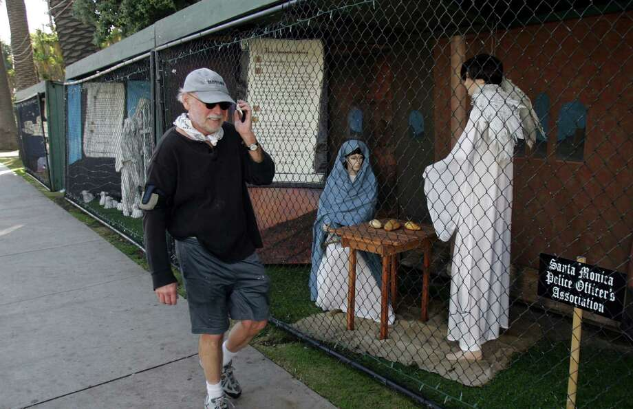 A man walks past Nativity scenes last December in Santa Monica, Calif. Atheist activist Damon Vix last year won two-thirds of the booths in the city-sponsored lottery for spaces in the life-sized Nativity display. Photo: Ringo H.W. Chiu, FRE / FR170512 AP