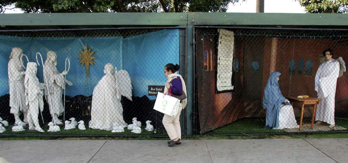 """FILE - In this Dec. 13, 2011 file photo, a woman walks past a two of the traditional displays showing the Nativity scene along Ocean Avenue at Palisades Park in Santa Monica, Calif. Avowed atheist Damon Vix last year won two-thirds of the booths in the annual, city-sponsored lottery to divvy up spaces in the live-sized Nativity display. But he only put up one thing: A sign that read """"Religions are all alike - founded on fables and mythologies."""" Vix left the rest of his allotted spaces empty, and in so doing, upended a Christmas tradition that began in Santa Monica nearly 60 years ago. (AP Photo/Ringo H.W. Chiu, file)"""