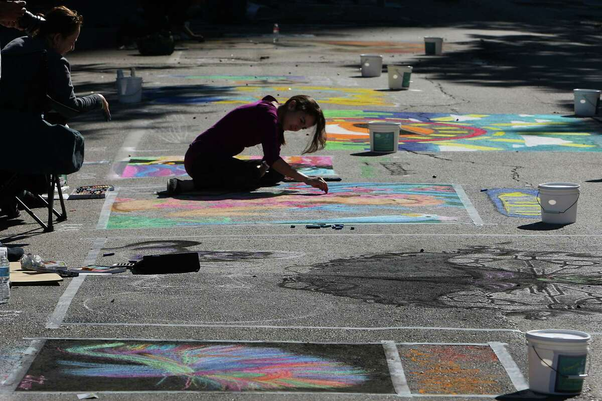 Natalia Rodriguez works on her chalk art piece Sunday during the Via Colori art festival in downtown.