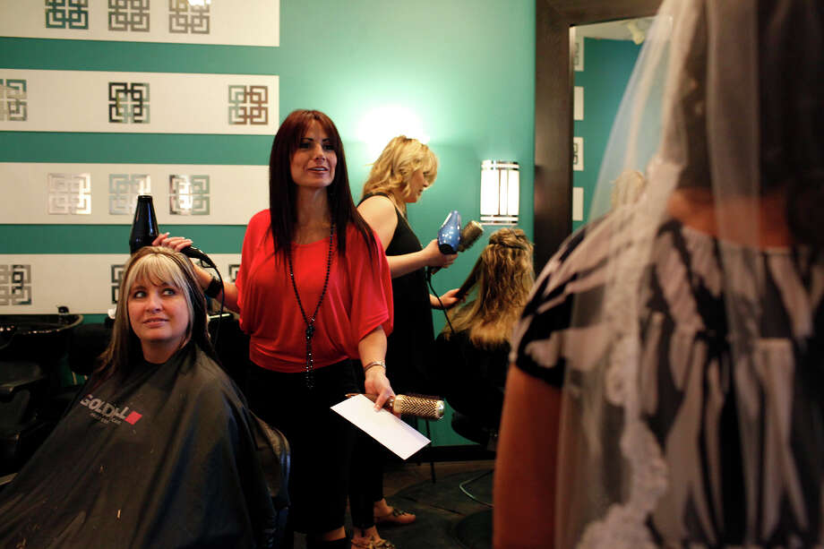 Artistic Edge co-owner Shannon McCarthy, center, says goodbye to customer Tina Hall, far right, who had her hair done for her bridal portraits, while working on client Dara Raborn, left, at the San Antonio salon this month. Photo: Lisa Krantz, Staff / © 2012 San Antonio Express-News