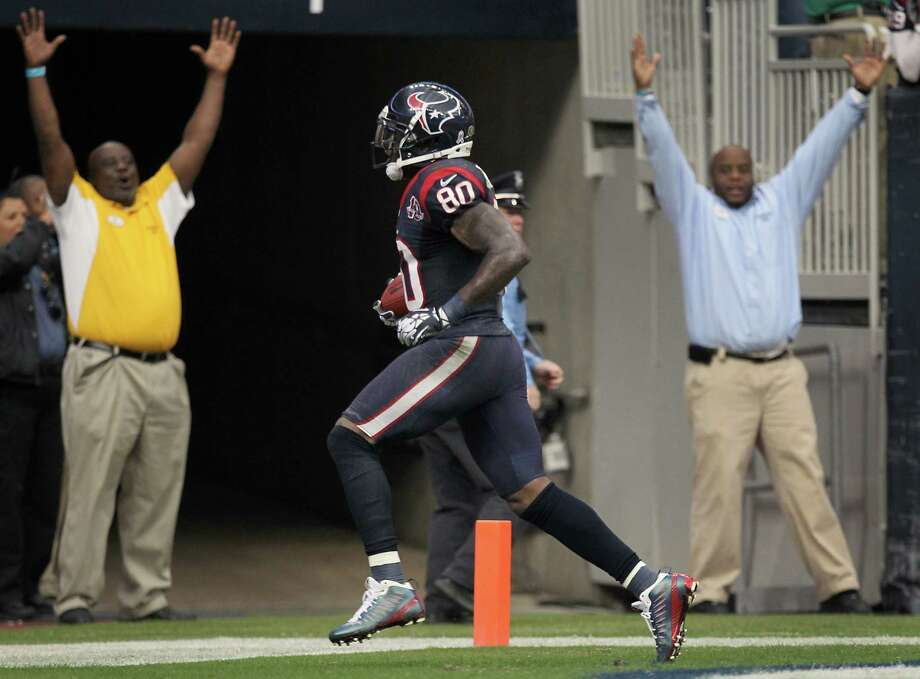As a couple of unofficial officials signal touchdown, Texans receiver Andre Johnson breaks away from the Jaguars for the game-winning score in overtime. Johnson finished with 14 catches for 273 yards. Photo: Nick De La Torre, Staff / © 2012  Houston Chronicle
