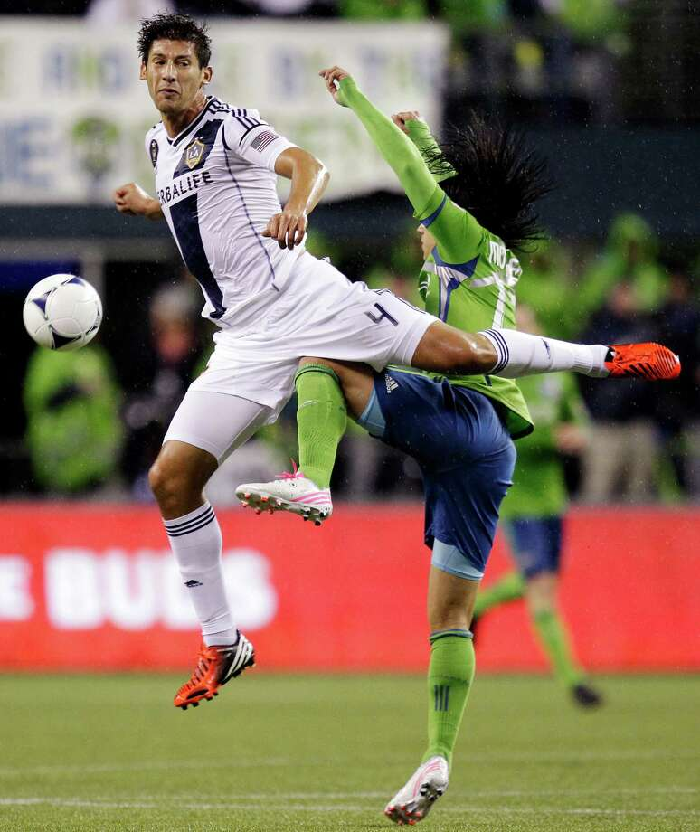 Seattle Sounders' Fredy Montero, right, goes up with Los Angeles Galaxy's Omar Gonzalez (4) for the ball in the first half of the MLS Western Conference championship soccer match, Sunday in Seattle. (AP Photo/Ted S. Warren) Photo: Associated Press