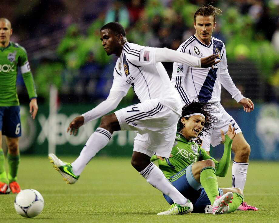 Seattle Sounders' Fredy Montero, second from right, goes down as he battles with Los Angeles Galaxy's David Beckham, right, and Edson Buddle, left, for the ball in the first half of the MLS Western Conference championship soccer match, Sunday in Seattle. (AP Photo/Ted S. Warren) Photo: Associated Press