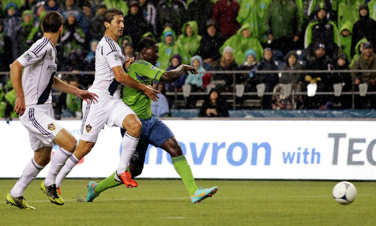 Seattle Sounders' Eddie Johnson, right, kicks a goal ahead of Los Angeles Galaxy's Tommy Meyer, left, and Omar Gonzalez, second from left, in the first half of the MLS Western Conference championship soccer match, Sunday, Nov. 18, 2012, in Seattle. (AP Photo/Ted S. Warren)