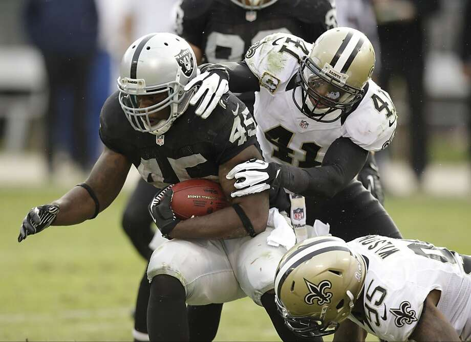 Oakland Raiders fullback Marcel Reece carries the ball before being stopped by New Orleans Saints strong safety Roman Harper (41) and defensive end Martez Wilson (95), during the third quarter of an NFL football game in Oakland, Calif., Sunday, Nov. 18, 2012. (AP Photo/Ben Margot) Photo: Ben Margot, Associated Press