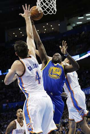 Draymond Green splits Nick Collison (4) and Kevin Martin on his way to the basket. Photo: Sue Ogrocki, Associated Press