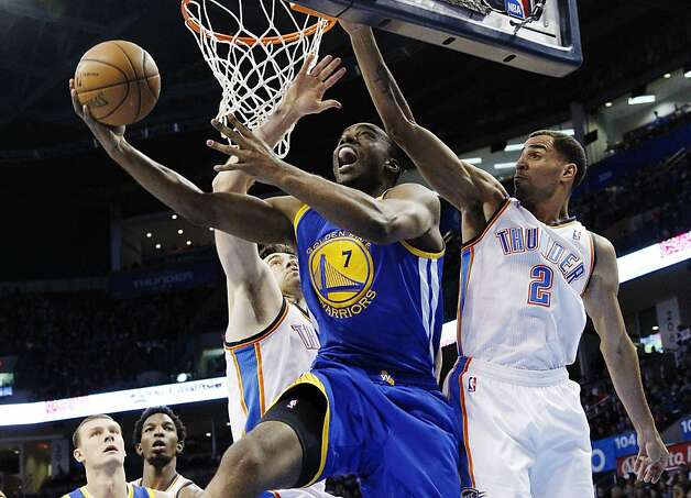 Golden State Warriors forward Carl Landry (7) shoots between Oklahoma City Thunder forward Nick Collison, left, and guard Thabo Sefolosha (2) in the first quarter of an NBA basketball game in Oklahoma City, Sunday, Nov. 18, 2012. (AP Photo/Sue Ogrocki) Photo: Sue Ogrocki, Associated Press