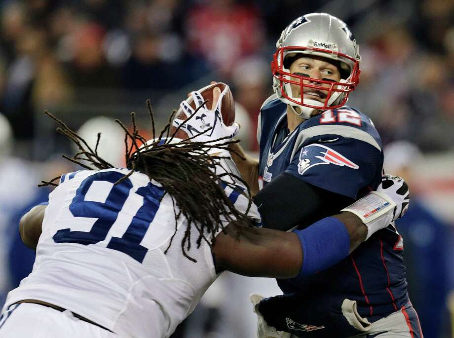 New England Patriots quarterback Tom Brady (12) eludes Indianapolis Colts defensive end Ricardo Mathews (91) to get a pass off during the second quarter of an NFL football game at Gillette Stadium in Foxborough, Mass., Sunday, Nov. 18, 2012. (AP Photo/Charles Krupa) Photo: Charles Krupa