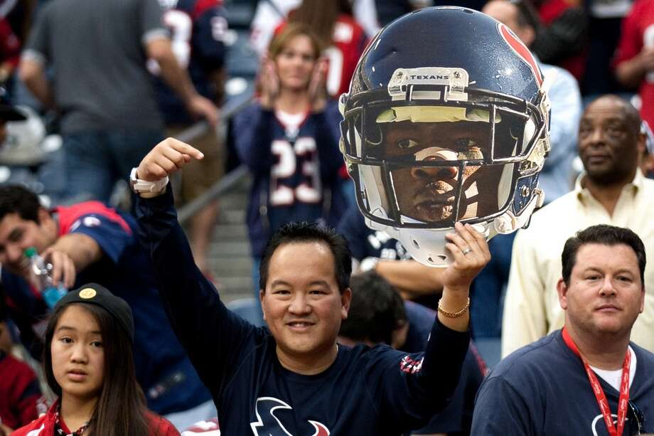 A Houston Texans holds up a giant Andre Johnson head after Johnson scored the game-winning touchdown. (Brett Coomer / Houston Chronicle)