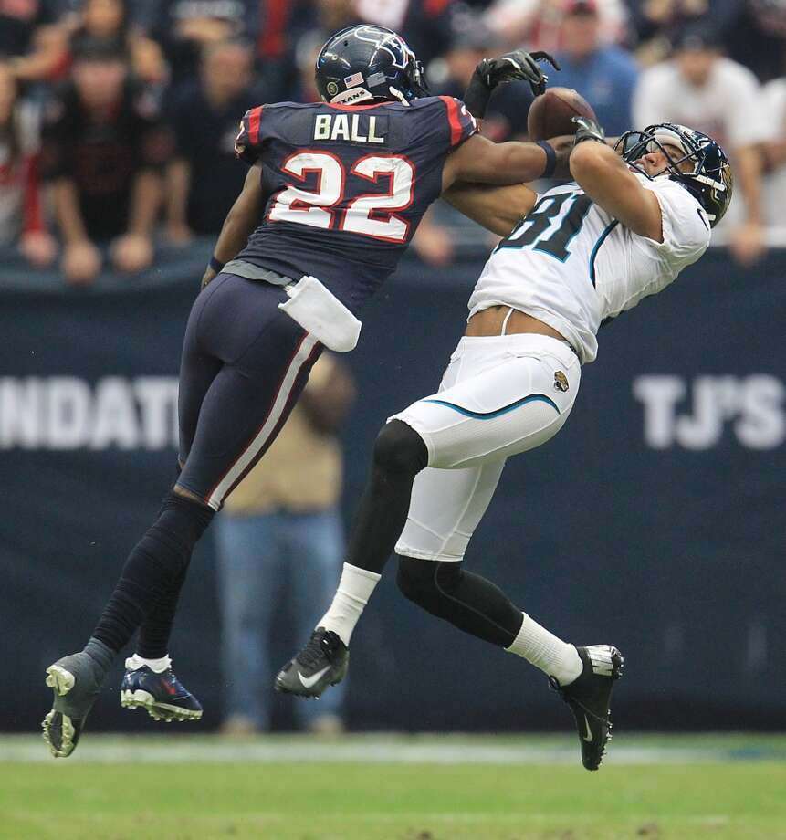 Jaguars wide receiver Laurent Robinson (81) gets the ball knocked away from him by Texans defensive back Alan Ball (22). (Karen Warren / Houston Chronicle)