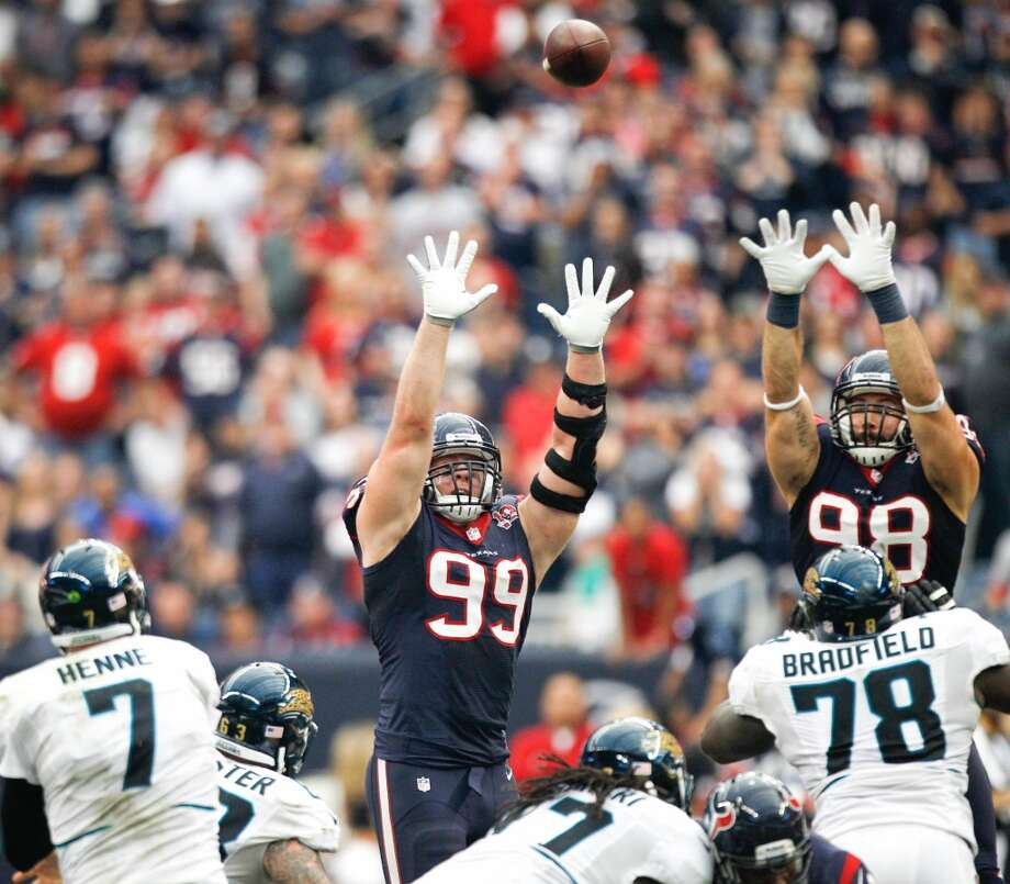 Texans defensive end J.J. Watt (99) and outside linebacker Connor Barwin (98) leap up to defend a pass by Jaguars quarterback Chad Henne during overtime. (Karen Warren / Houston Chronicle)