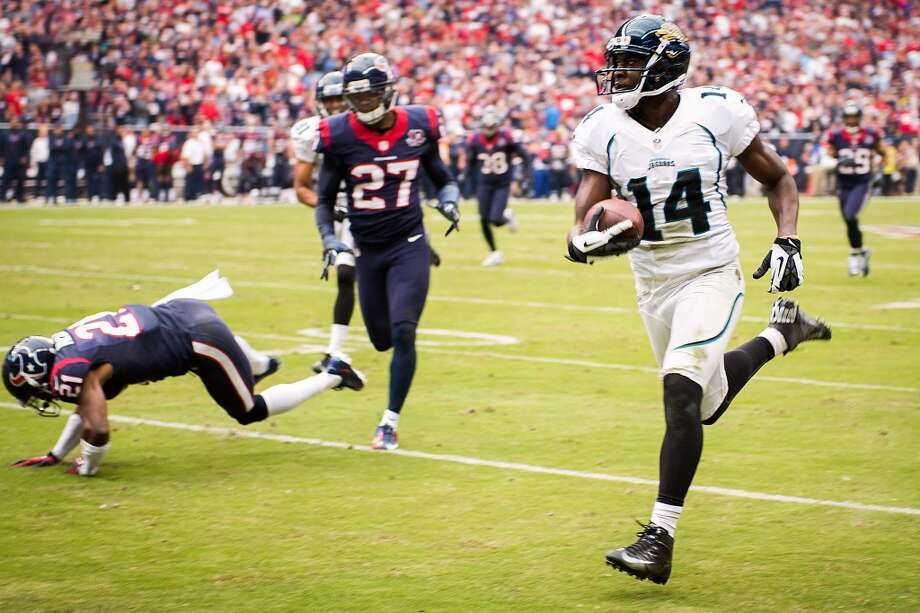 Jaguars wide receiver Justin Blackmon (14) races 81-yards past Texans defensive backs Quintin Demps (27) and Brice McCain (21. (Smiley N. Pool / Houston Chronicle)