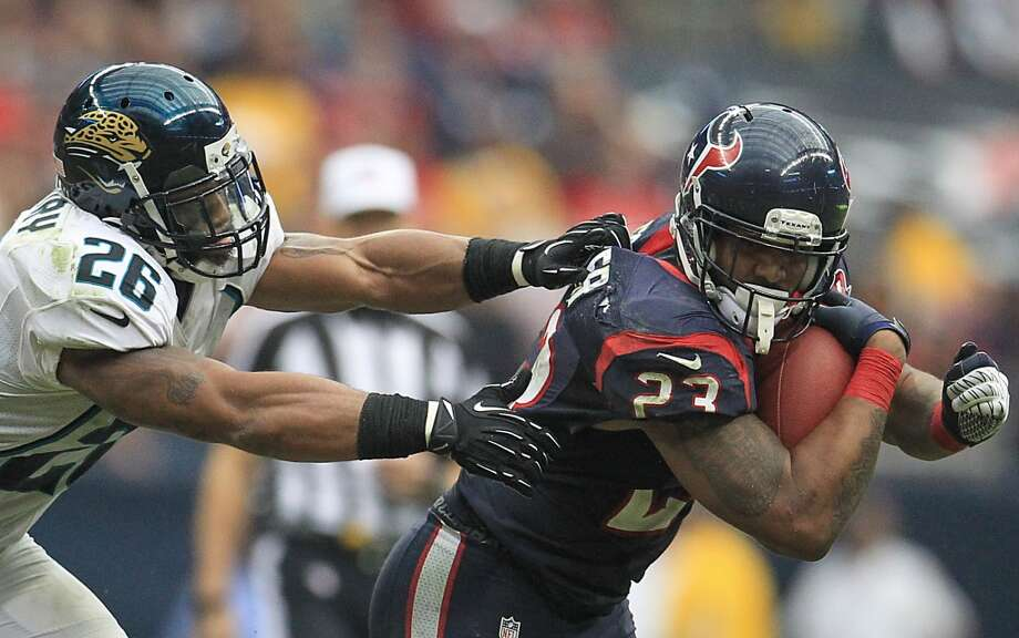 Texans running back Arian Foster (23) runs as he tries to avoid getting tackled by Jaguars strong safety Dawan Landry (26) during the fourth quarter. (Karen Warren / Houston Chronicle)