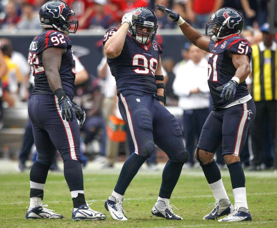 Texans defensive end J.J. Watt (99) celebrates his sack of Jaguars quarterback Chad Henne with nose tackle Earl Mitchell (92) and linebacker Darryl Sharpton (51) during the fourth quarter. (Brett Coomer / Houston Chronicle)