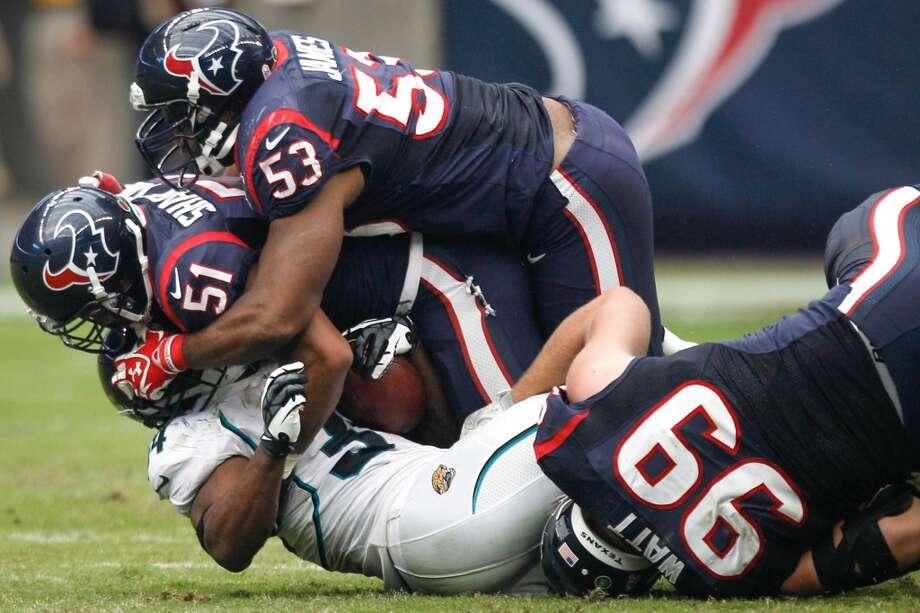 Texans linebackers Darryl Sharpton (51), Bradie James (53) and defensive end J.J. Watt (99) stop Jacksonville Jaguars running back Jalen Parmele (34) for a loss during the third quarter (Brett Coomer / Houston Chronicle)
