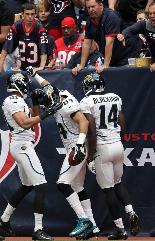 Texans fans look on as Jacksonville wide receiver Cecil Shorts (84) celebrates with  Laurent Robinson (81) and Justin Blackmon (14) after scoring on a 67-yard touchdown reception during the second quarter. (Nick de la Torre / Houston Chronicle)