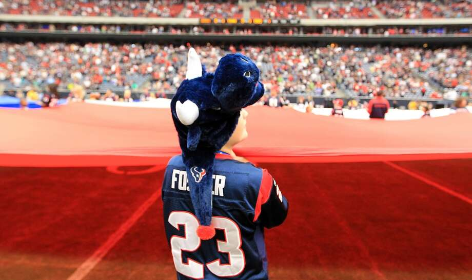Bryan Clarkson, 9, holds the flag before the start of the game. (Karen Warren / Houston Chronicle)