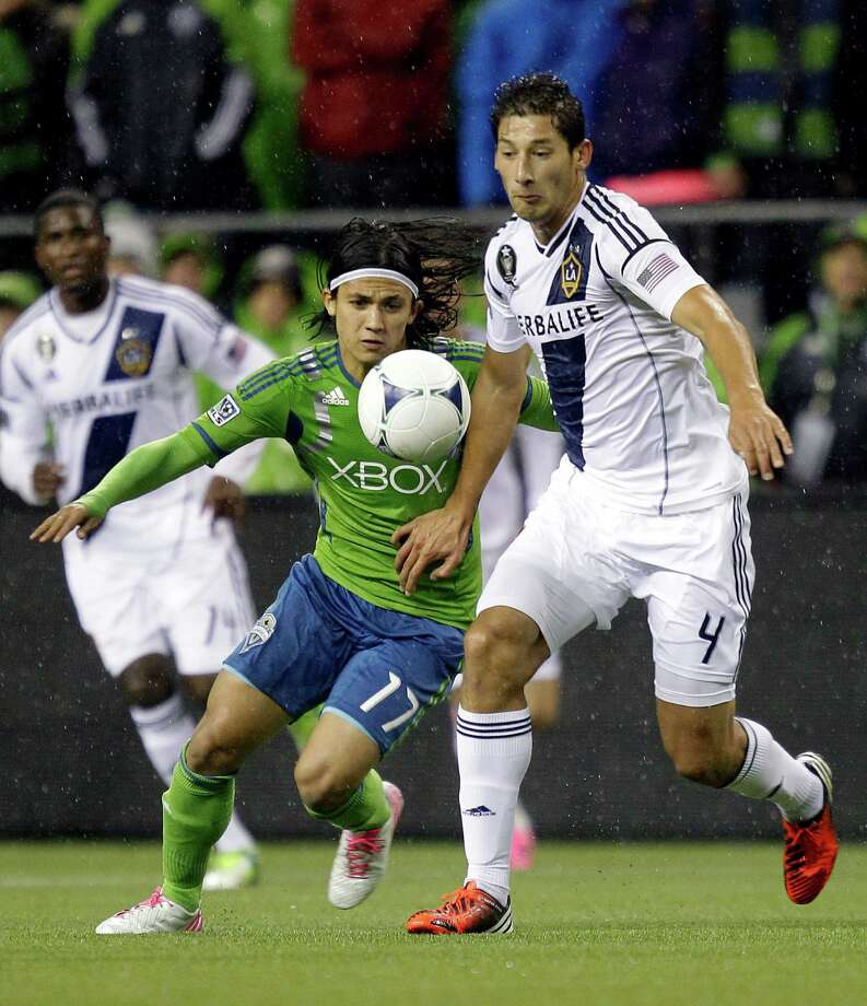 Seattle Sounders' Fredy Montero, left, battles with Los Angeles Galaxy's Omar Gonzalez (4) for the ball in the first half of an MLS Western Conference championship soccer match, Sunday. (AP Photo/Ted S. Warren) Photo: Associated Press