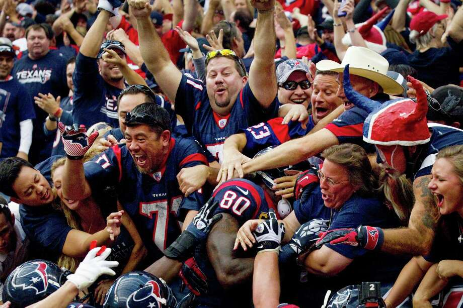Texans fans swarm wide receiver Andre Johnson (80) after he scored the game-winning touchdown on a 48-yard reception against the Jacksonville Jaguars during overtime at Reliant Stadium on Sunday, Nov. 18, 2012, in Houston. The Texans beat the Jaguars 43-37. Photo: Brett Coomer, Houston Chronicle / © 2012  Houston Chronicle