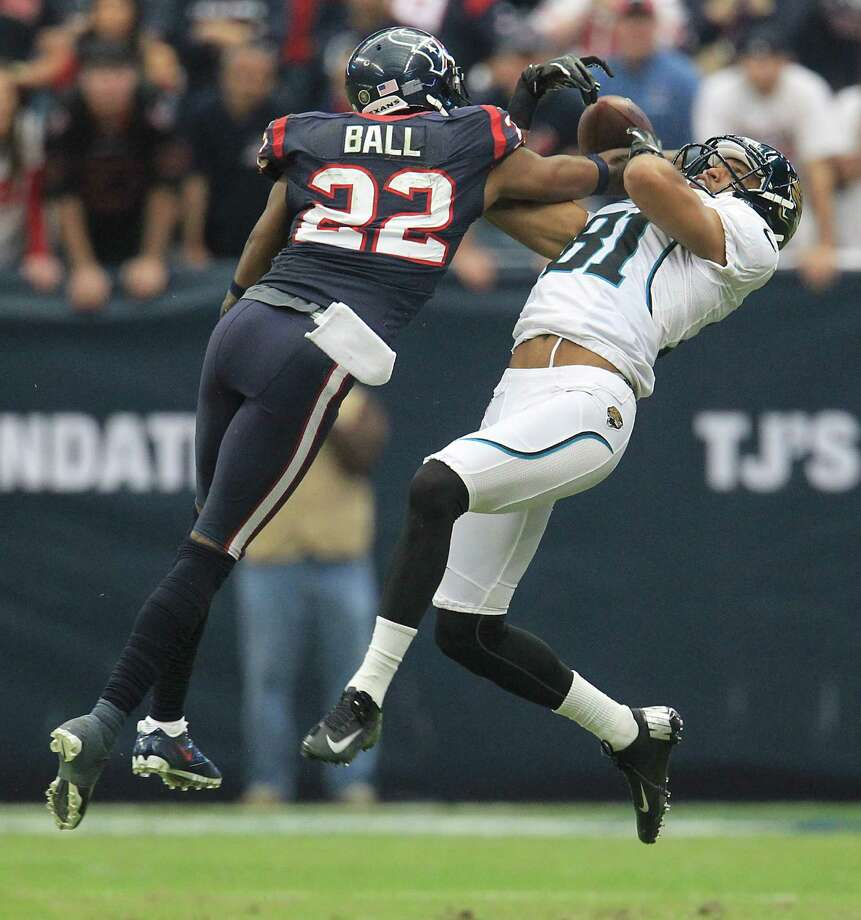 Jaguars wide receiver Laurent Robinson (81) gets the ball knocked away from him by Texans defensive back Alan Ball (22). Photo: Karen Warren, Houston Chronicle / © 2012  Houston Chronicle